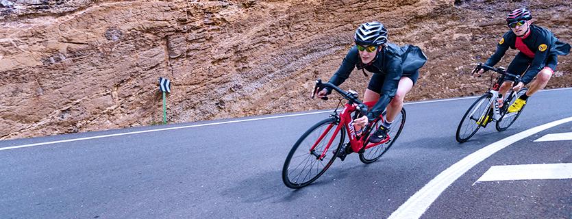 Ein Mann und eine Frau fahren auf Rennrädern einen Bergpass herunter. Sie nutzen CicloSport Fahrradcomputer.