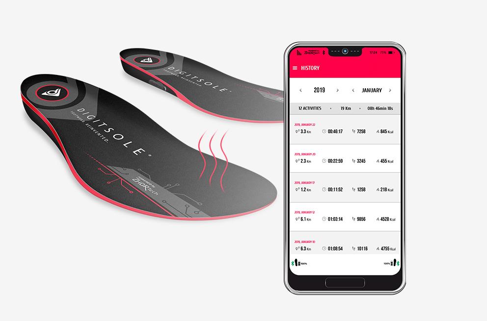 Produktbild von Digitsole. Zwei Heizsohlen sind neben einem Smartphone mit der passenden App zu sehen