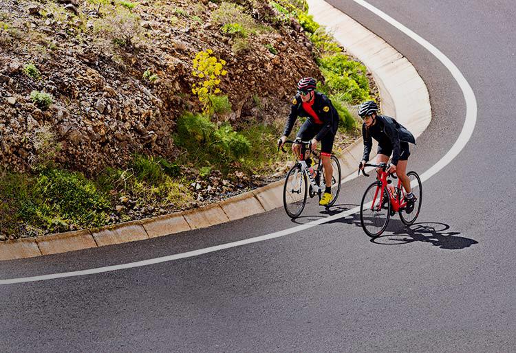 Zwei Radfahrer fahren mit CicloSport-Produkten eine steile Straße hinauf